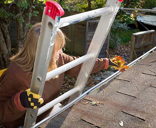 A senior woman on a ladder cleans leaves and twigs from rain gutters or eavestrough. Photo is from above on the roof looking down. Good copy space.