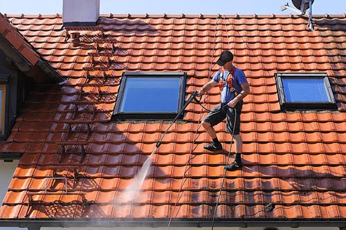 Worker is cleaning the roof and rainwater gutter with high pressure.